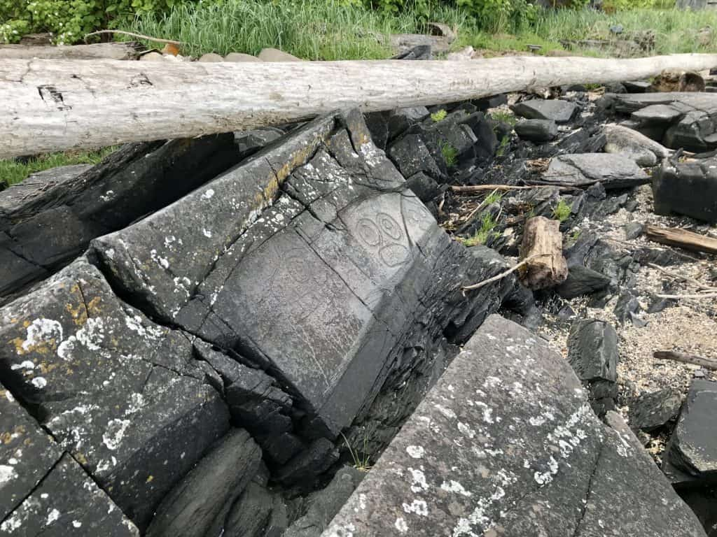 Carving relic amongst rocks, grass and a fallen log in Petroglyph State Historic Park, Wrangell, Alaska.