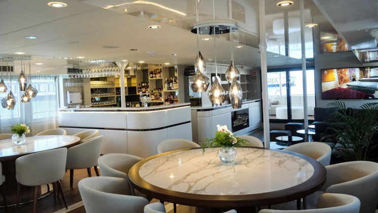 Dining room with white marble tables, beige padded chairs, white leather-wrapped bar & modern glass pendant lights on deluxe yacht Aurelia.