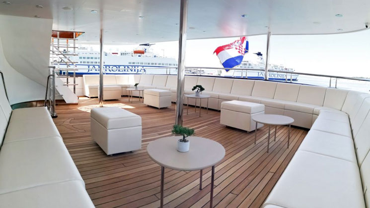 Middle-deck exterior seating area with wraparound white leather couch, teak decking & white leather ottomans, aboard Aurelia yacht.