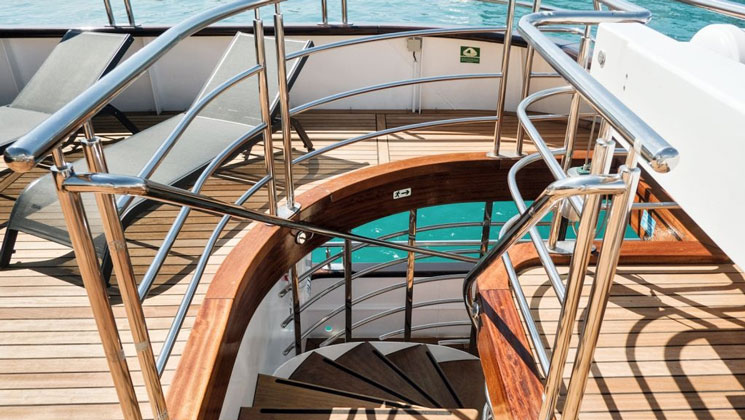 View down teak deck stairs on Aurelia deluxe yacht, with beige chaise lounge chairs & turquoise water beside.