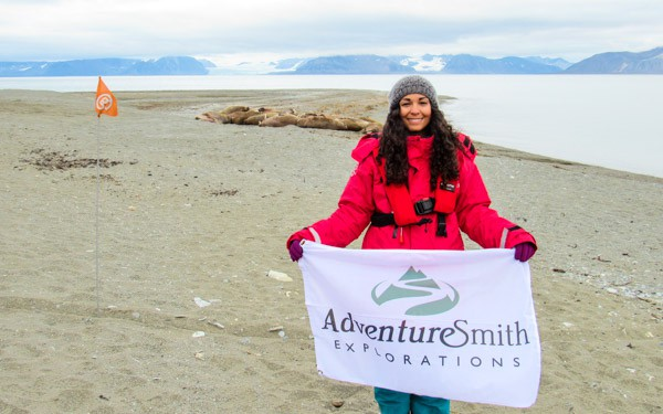 Single traveler in a red jacket holds an AdventureSmith flag on an Arctic beach