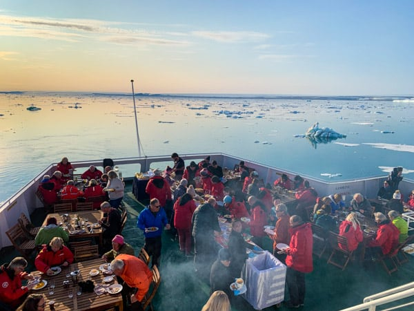 An outdoor barbeque in the Arctic aboard Expedition with guests seated at tables