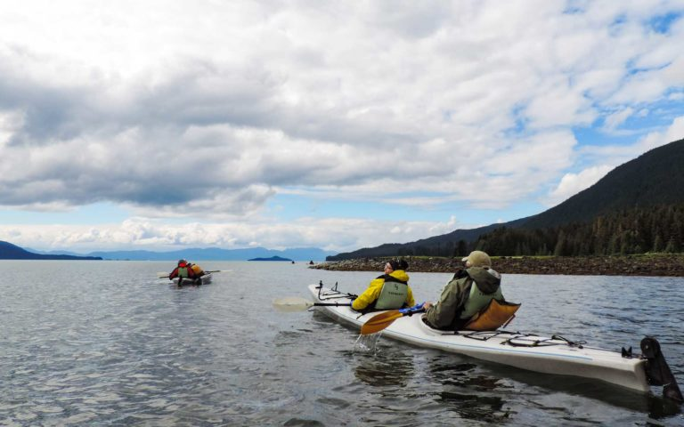 small ship cruise travelers sitting in kayaks among the san juan islands in the pacific northwest with white clouds above