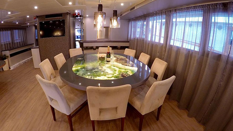Dining room aboard yacht Rhapsody with art deco green marble round table, beige padded chairs, pendant lights, wood floor & windows.
