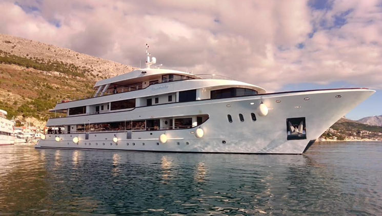 View from the water of the large white yacht Aurelia sitting in the harbor beside green hills on a partly cloudy day.
