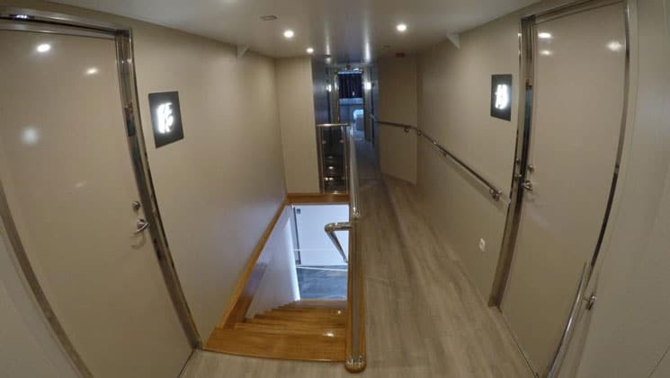Hallway on yacht Rhapsody with shiny beige walls, wood staircase, light-up cabin numbers & recessed lighting.