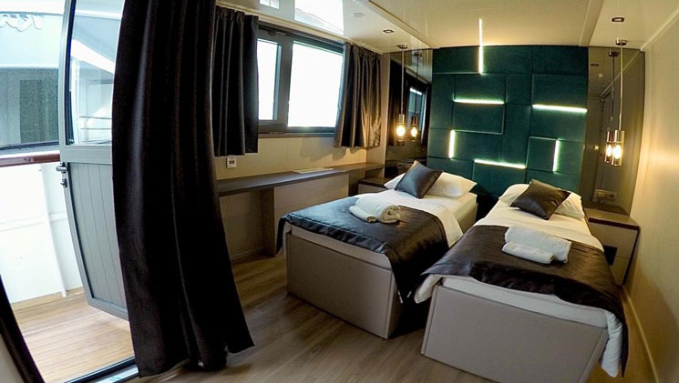 VIP Upper Deck cabin on yacht Rhapsody, with 2 twin beds, wood floor, dark curtains, lit up turquoise headboard & pendant lights.