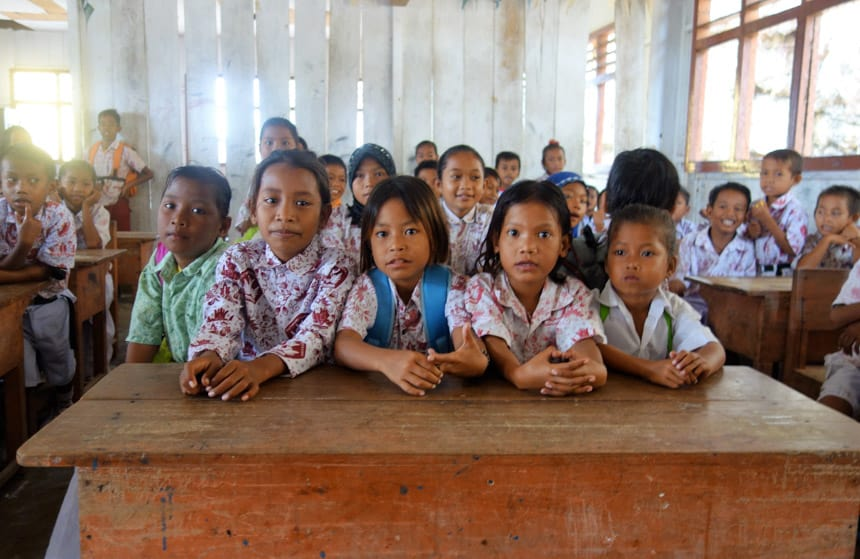 Indonesia children sitting at a wooden school desk in their patterned uniforms.