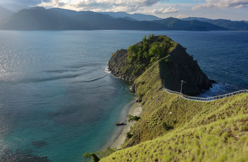 remote indonesia island with a zodiac on the beach and green hillsides
