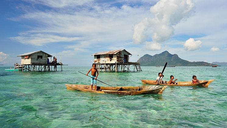 Kids in sea gypsy village Bajau Laut, Indonesia, on a wooden boat in front of houses on stilts over emerald water on a sunny day.