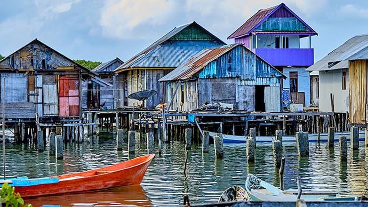 Dilapidated village painted in bright colors and standing on wooden stilts above the water in Indonesia.