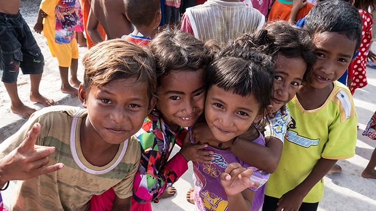 Village children leaning in and smiling for the camera in Sulawesi, Indonesia.