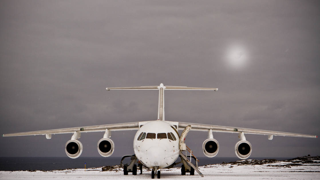 Antarctica Express Air Cruise jet landed on snowy King George Island with the sun behind gray clouds.