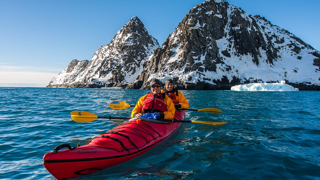 Kayakers in a red tandem kayak floating on ice-blue water with snowy island mountains in the background on an Antarctica Express Air Cruise.