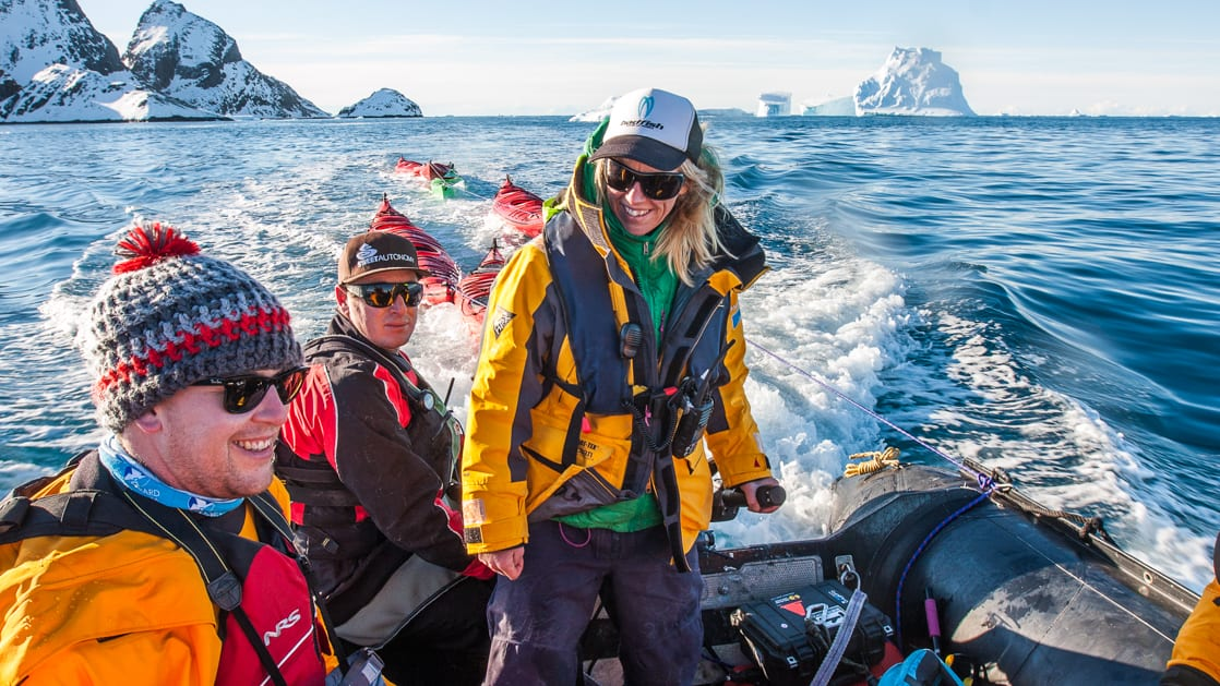 Antarctic travelers Zodiac cruising with guide standing and steering the inflatable boat & mountains in the background on a sunny day.
