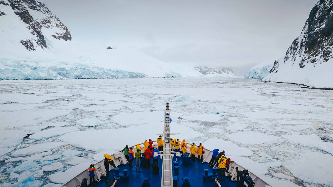 Antarctica travelers stand at bow of ship to view iceberg-laden waters & snowy mountains on a cloudy day.