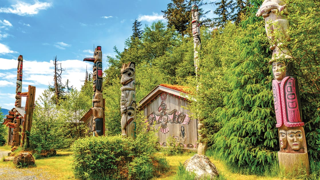 Native American Totems and Clan Houses in Ketchikan, Alaska, set against bright green forest and blue sky.