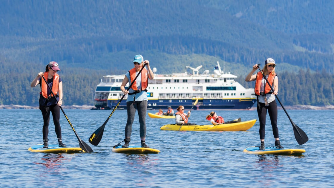 Three women stand-up paddleboarding with a National Geographic expedition ship in the background, on a sunny day.