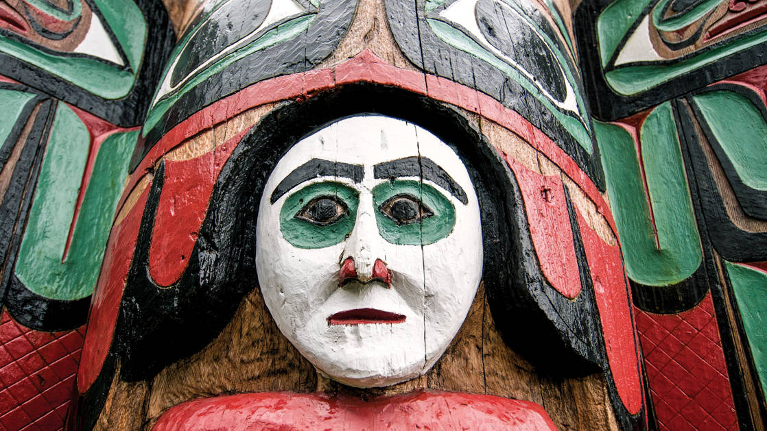 Close up on one section of a totem pole in Ketchikan Alaska, showing a white face with red and green accents.