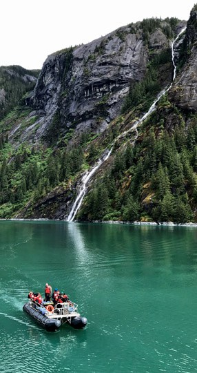 a daily excursion aboard an Alaska small ship cruise, a group enjoys a skiff ride through the teal waters of Alaska's Inside Passage, beyond them is a lush mountainside with a waterfall coming from the cliff.