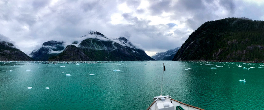 bow of ship cruising into scenic mountain vista and teal waterway on alaska small ship cruise