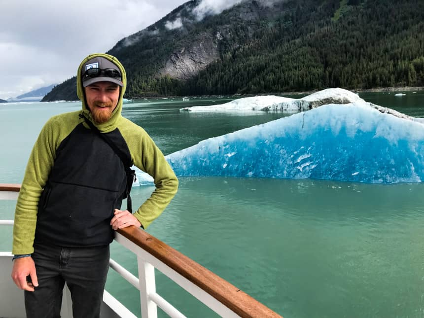 Adventure specialist on bow of alaska small ship in front of forested mountain range and bay water filled with floating teal icebergs