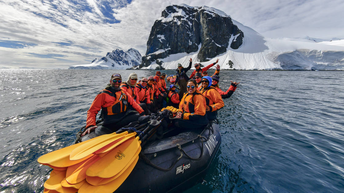 A group of Antarctica travelers in brightly colored jackets waves from a Zodiac with yellow kayak paddles on the bow, on a sunny day during the Antarctic Southern Latitudes expedition.