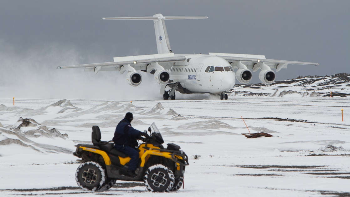 A man rides a yellow all terrain vehicle across Antarctic tundra, beyond him a white charter plane sits on a landing strip in Antarctica.