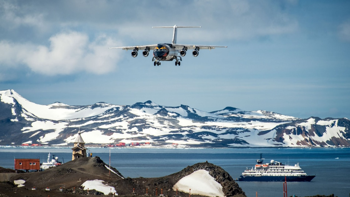For an express fly cruise itinerary an Antarctica expedition ships floats in the ocean while a charter plane flies through the blue sky headed to the landing strip below.