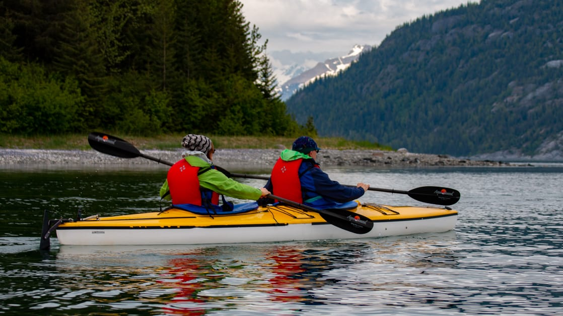 Tandem kayakers paddling on a Southeast Alaska small ship cruise, with green mountains and rocky shoreline in the background.