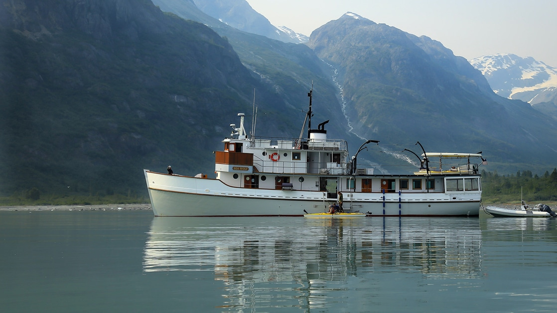 Alaska Small ship the Sea Wolf floats in Glacier Bay in front of a mountain range, kayakers paddle around the boat.