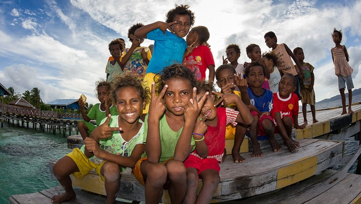 West Papuan children in Arborek Village pose for a picture on the dock during the Aqua Blu Raja Ampat Indonesia culture cruise.