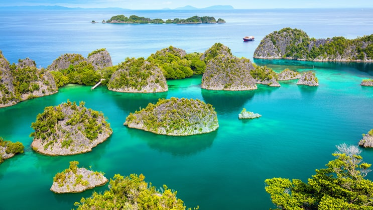 Aerial view of limestone karst gumdrop islands in emerald waters as seen on the Aqua Blu Raja Ampat Indonesia luxury cruise.