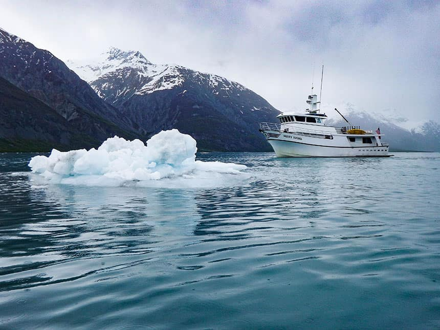 Small ship cruising in alaska teal waters with a iceberg floating in the forefront and snow capped mountains in the bag