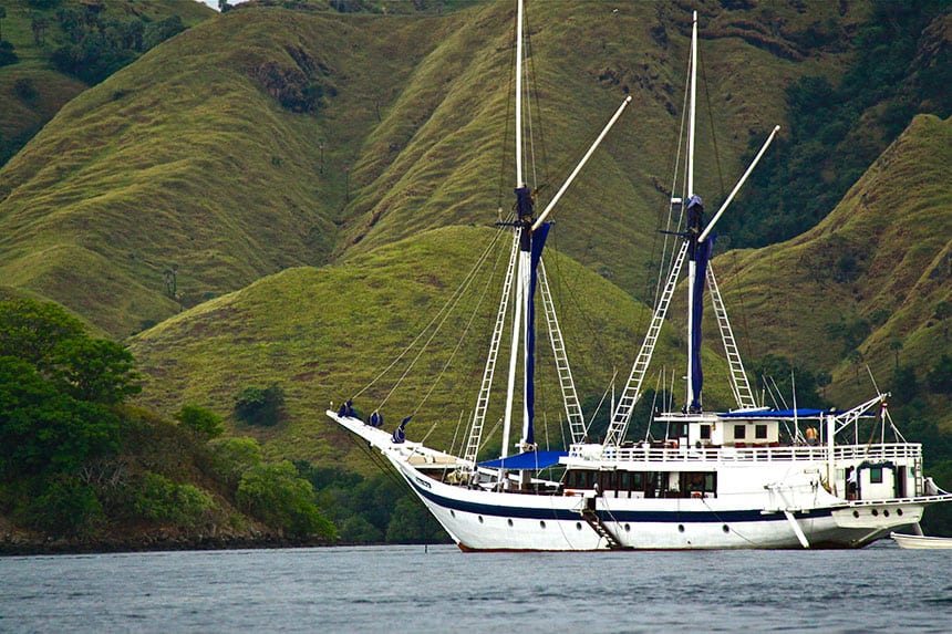a white Indonesian wooden sailing ship against green lush mountain side floating in the ocean