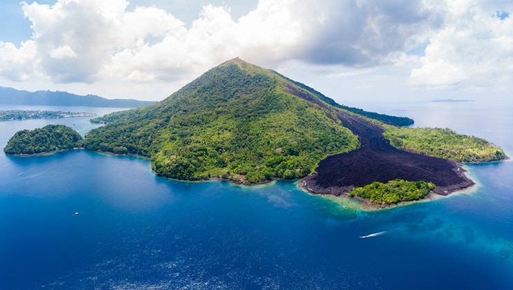 Aerial view of the Gunung Api volcano, covered in bright green vegetation & surrounded by deep blue sea, seen during the Aqua Blu Ambon & Spice Islands Cruise in Indonesia.