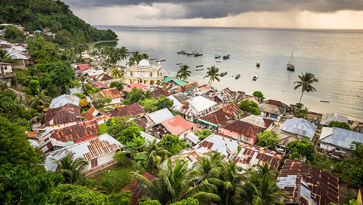 A seaside village of weathered homes tucked into Run Island's green hillside, seen during the Aqua Blu Ambon & Spice Islands Cruise in Indonesia.