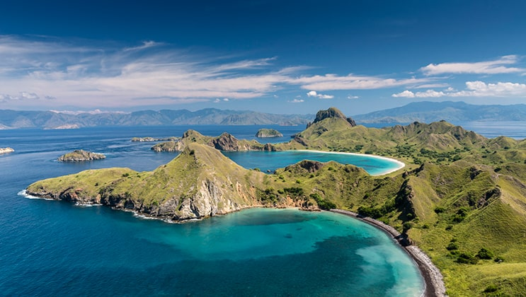 Aerial panorama of Komodo National Park in Flores island with green volcanic hilltops & turquoise waters as seen on the Aqua Blu Bali to Flores cruise.