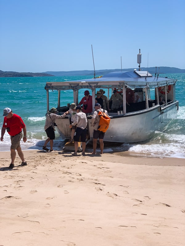 The small passenger vessel with a overhead cover and open air windows,, beaches ashore a sandy beach and allows guests to disembark. Behind the vessel a teal ocean and a bright blue sky