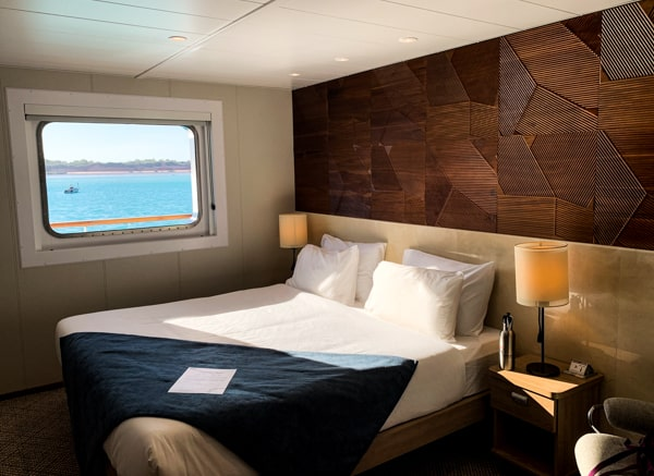 Inside of the Coral Adventurer wooden walls with artistic pattern horizontal, window opening to the teal ocean
