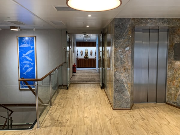 Elevator aboard Coral Adventurer, light wooden floor with stone granite walls and a silver metal elevator