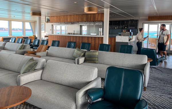 Lounge area of Coral Adventurer, grey love seats with dark teal leather chairs