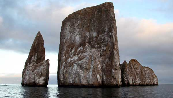 Kicker Rock in the Galapagos seen close-up with the sun setting in a cloudy sky