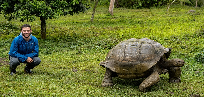 Green lush landscape with galapagos tortoise and traveler kneeling next to it