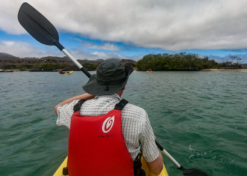 Blue sky and teal water as a kayaker paddling through the ocean in the Galapagos wearing a red life jacket and a grey wide brim ha