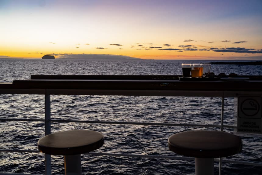 Stools and a high top table holding a selection of beers overlooking the back of a small ship with a view of the orange purple sunset