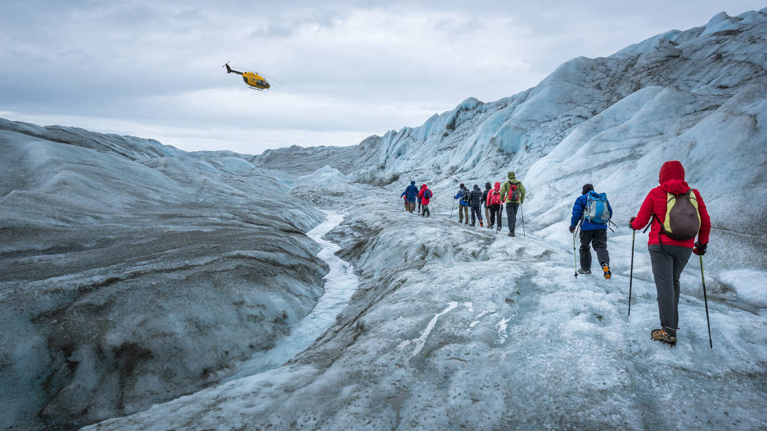 Glacier hikers on the icecap near Kangerlussuaq, with a helicopter in the sky, during the Greenland Adventure cruise by land, sea and air.