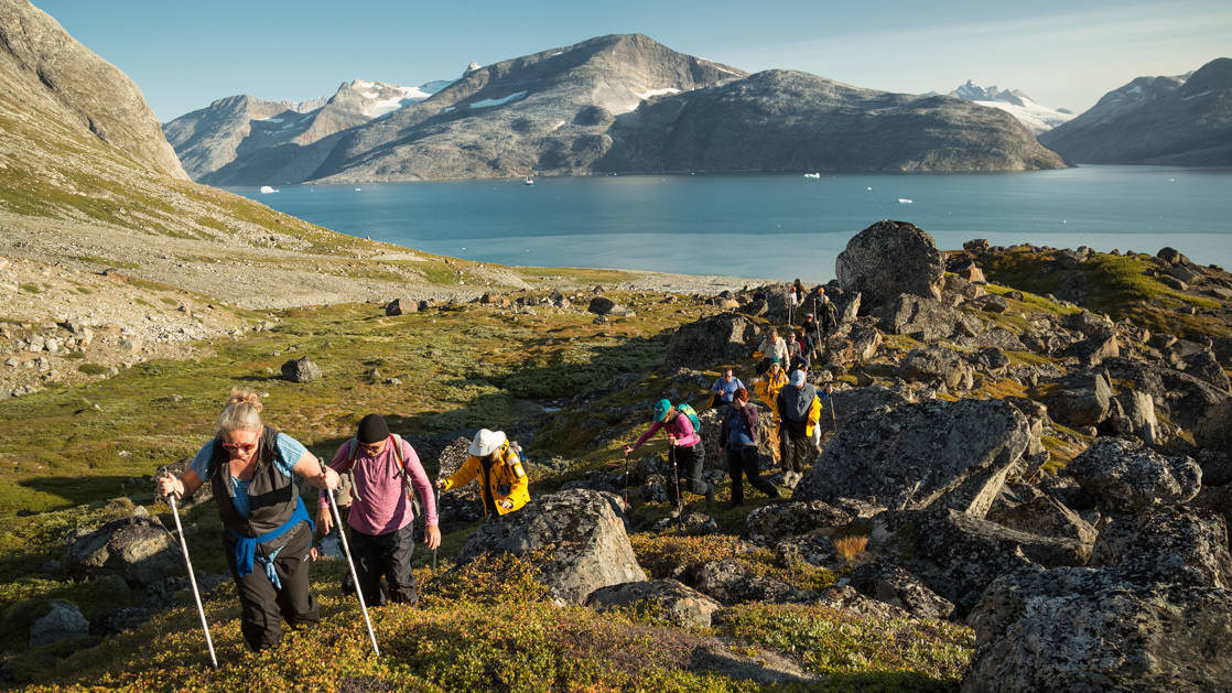 A line of hikers walk over rocky, grassy knolls, on a sunny day, during the Greenland Adventure cruise by land, sea and air.