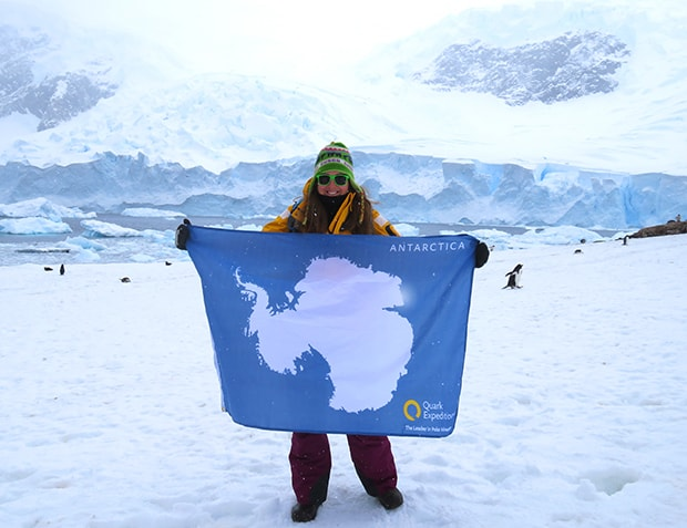 In front of an icy white landscape a female traveler wears a yellow expedition jacket and holds a blue and white flag of antarctica, she is celegrating reaching her 7th continent via Antarctica cruise
