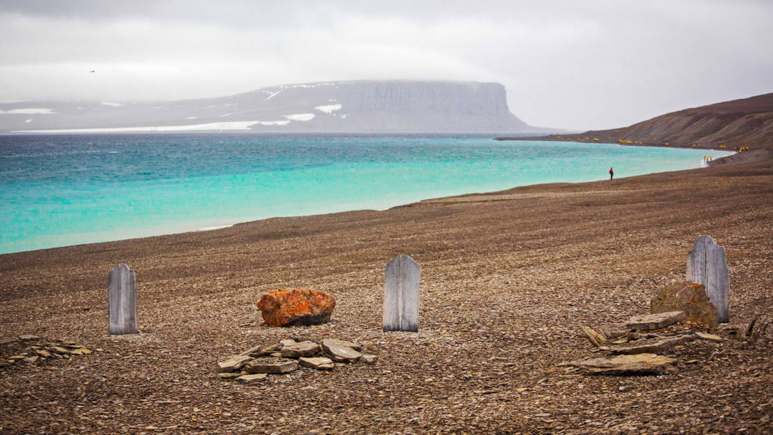 Beechey Island with 3 graves of explorers on a misty day with turquoise water along the brown, rocky shoreline, seen during The Northwest Passage Canadian High Arctic voyage.